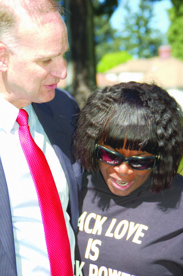 Multnomah County District Attorney Rod Underhill embraces Perlia Bell, the mother of Asia Bell, a Portland woman who died of gun violence in 2002.