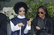 U.S. pop singer Prince, left, watches the fourth round match of the French Open tennis tournament between Spain's Rafael Nadal and Serbia's Dusan Lajovic at the Roland Garros stadium, in Paris, France, Monday, June 2, 2014. (AP Photo/Michel Spingler)