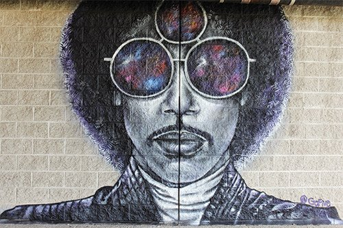 Artist GoFive painted this mural behind Madison Park High School last week in tribute to legendary musician Prince, who died recently at 57.