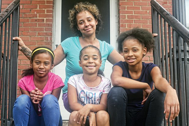 Tara Spencer sits on the porch of her apartment on Creighton Road with her daughters, from left, Dionicia, 8, La-Taja, 6, and Japria, 12.