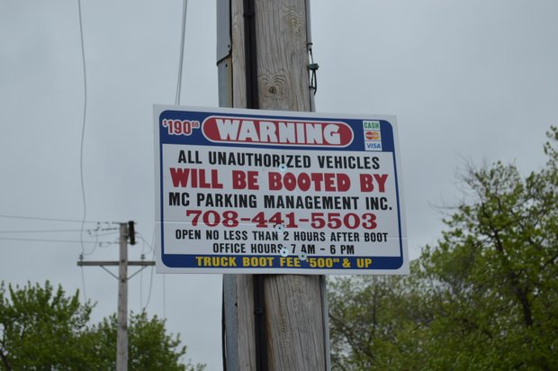 Signs at the Marycrest Shopping Plaza warn shoppers that their cars could be immobilized for parking in the wrong spot.