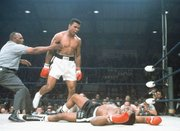 Heavyweight champion Muhammad Ali stands over fallen challenger Sonny Liston, shouting and gesturing shortly after dropping Liston with a short hard right to the jaw in the first round of their 1965 title fight in Lewiston, Maine, one of sports' most iconic moments.