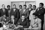 "Sports stars take part in the 1967 ""Ali Summit"" in Cleveland to show support for the boxing champ's refusal to be drafted. Mr. Ali, seated second from left, was joined by, seated from left, Bill Russell, Boston Celtics; Jim Brown, Cleveland Browns, and then college star Lew Alcindor Jr., later L.A. Lakers great Kareem Abdul-Jabbar. Standing from left: Ohio Congressman Carl Stokes; Walter Beach, Cleveland Browns; Bobby Mitchell, Washington NFL team; Sid Williams, Cleveland Browns; Curtis McClinton, Kansas City Chiefs; Willie Davis, Green Bay Packers; Jim Shorter, former Cleveland Browns player and John Wooten, Cleveland Browns."