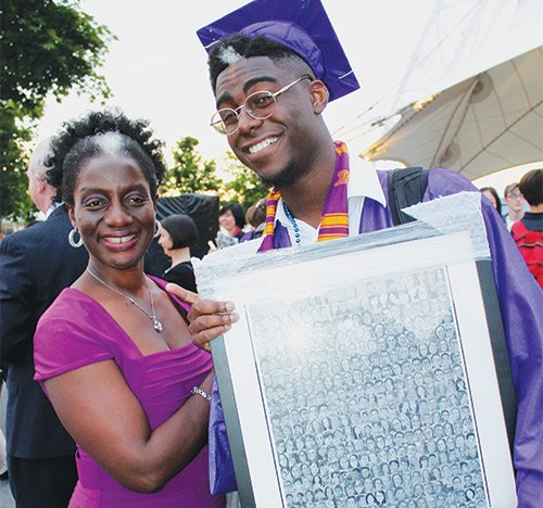 Boston Latin graduate Philip Sossou, shown with his mom, was presented a framed photograph depicting his drawings of his classmates with his diploma at graduation exercises for Boston Latin School on Monday evening, June 13 at the Blue Hills Bank Pavilion.