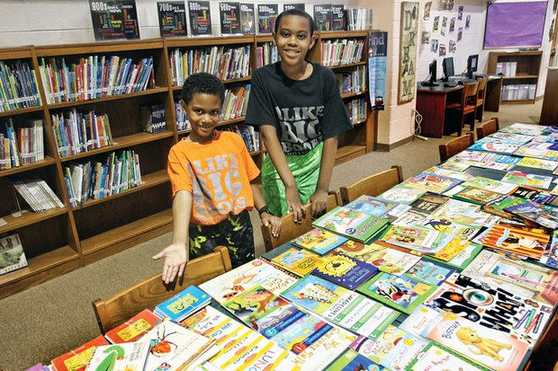 Brothers Jace, 7, left, and Jazz Miles, 10, show off some of the 1,400 books they collected to give to their fellow students at Richmond's Linwood Holton Elementary School. The boys' efforts mean that Holton's 600 students will have at least two books of their own to read during summer break.