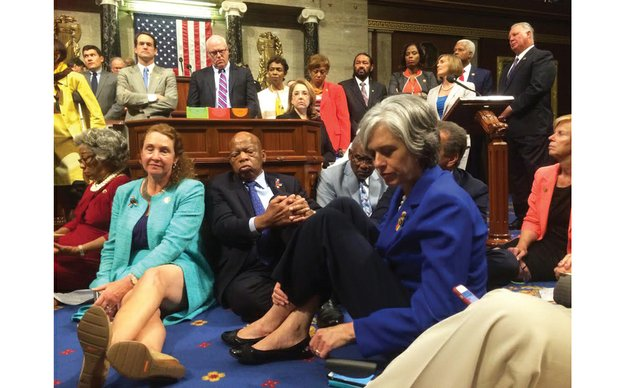 Rep. Katherine Clark of Massachusetts tweeted a photo from the floor of the U.S. House of Representatives on Wednesday showing the sit-in demanding common sense gun control legislation to keep suspected terrorists from buying guns and tightening background checks. Sitting on the floor in the center is Rep. John Lewis of Georgia, who led the historic action.