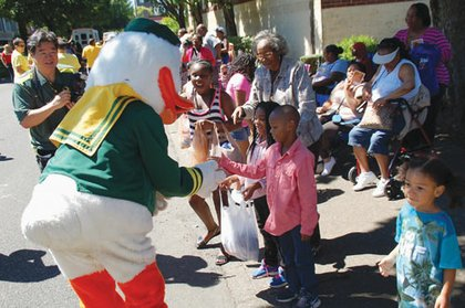 The Oregon Ducks mascot interacts with youth along Saturday's parade route.