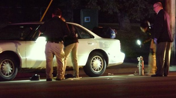 Police peer into the car that Philando Castile was riding in as a passenger when he was shot multiple times by an officer making a traffic stop in Falcon Heights, near the gates to the Minnesota State Fair grounds.. (Photo: Harry Colbert, Jr./Insight News)