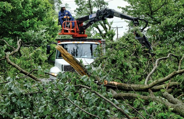 Cleanup is still underway after the June 16 storm. Here a city worker uses heavy machinery to pick up a mass of fallen limbs on Claremont Avenue. More than 900 city trees were toppled during the event, and some were weakened enough to fall days later.