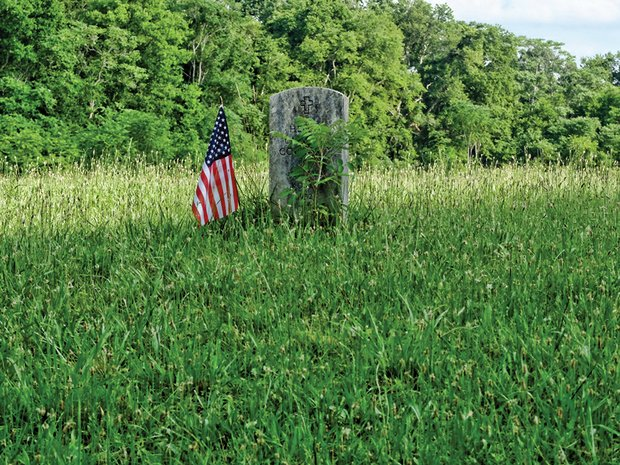 A flag marks a veteran's grave in private Evergreen Cemetery, located off Nine Mile Road in Eastern Henrico County. The Virginia Outdoors Foundation has launched an effort to preserve and protect the cemetery that dates to 1891.