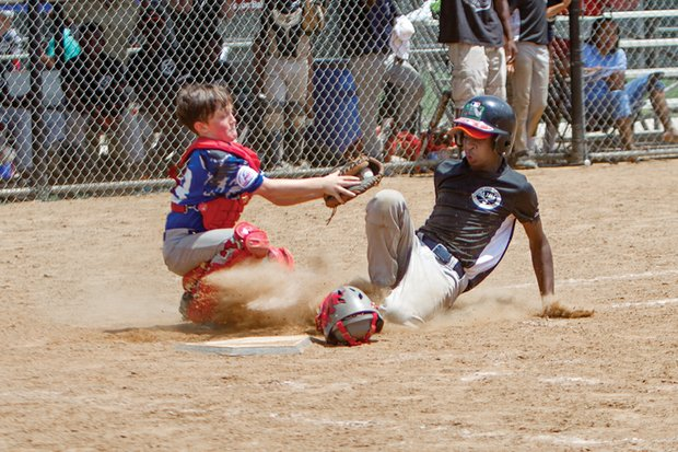 Deon Harns, right, of the Metropolitan Junior Baseball League team slides into base under the glove of Chesterfield Blue Sox catcher Britton Proffitt during the fourth annual Richmond Flying Squirrels Regional Youth Tournament last weekend at Harry G. Daniel Park at Ironbridge.