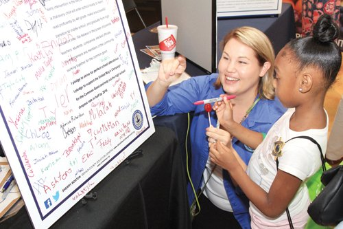 Lisa Moultrie of the DeKalb Solicitor General's Office helps a student sign Sherry Boston's Perfect Attendance Pledge.