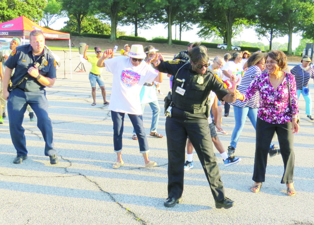 DeKalb Police Sgt. C. Dillard shares a light moment with a resident during a line dance at the National Night Out block party on Aug. 2 in the parking lot of the Gallery at South DeKalb in Decatur. There were 25 other events across DeKalb County.