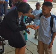 Turner Elementary School Assistant Principal Lisa Rosado greets a student and hands him a Nutri-Grain breakfast bar on Aug. 8, the first day of the extended school year for D.C. public schools.