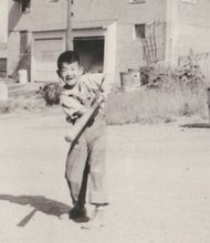 A young Japanese-American boy plays baseball in the alley of a temporary hostel in Seattle after his family became homeless after behind held in concentration camps in the U.S. during World War II.