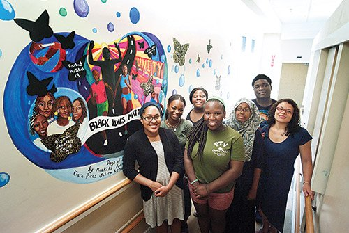 Interns from the Roxbury Youth Program, sponsored by the Unitarian Universalist's Urban Ministry, unveil their mural highlighting the power of community in support of the Black Lives Matter Movement. (l-r) Kiara Pires, Zhania Goode, Jalera Remy, Ionya Whyles, Mezki Ali, Andre Coker-Ryan and, supervising the work, artist/educator Darre Ann Gane-McCalla.