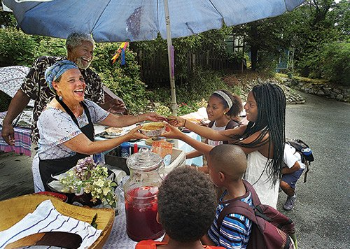 Sister Angela Paige and Brother Joe Cook hand food to Gabrielle Farrow, 13, as the community visited the Paige Academy in Roxbury to enjoy Ahmed's Table, an urban pop-up kitchen and garden-to-table market, over the weekend. Proceeds go to the Ahmed Cook Scholarship Fund. The Paige Academy provides a holistic approach to education, from birth to six years.