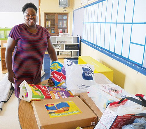 First grade teacher Shauntell Dunbar surveys a table full of supplies she purchased for her classroom at Young Achievers School of Science and Math in Mattapan. Many BPS teachers are spending more of their own money on supplies this year as schools grapple with budget constraints.