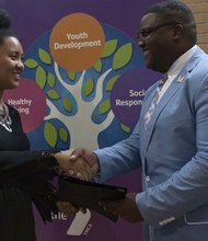 Asia Yoon (left) is congratulated by Derryck Fletcher, vice president of youth development of the Y in Central Maryland for successfully completing the seven-week summer internship with New Horizons II.