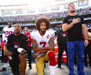 San Francisco 49ers quarterback Colin Kaepernick (center) has been kneeling instead of standing during the playing of the national anthem at NFL games to protest police brutality against African Americans.