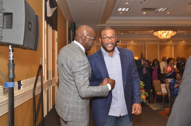Left: Tyler Perry (right) greets Nike exec Willie Gregory at the Coaches' Luncheon. (Photo: Tyrone P. Easley)