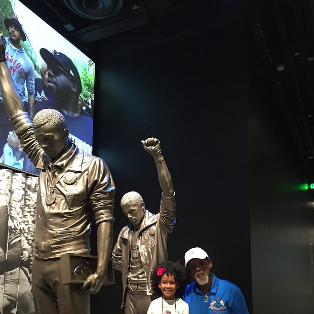 John Carlos stands by the sculpture depicting the iconic fist raise as he took to the winners' podium as a Bronze medalist at the 1968 Summer Olympics Games in Mexico City. He is pictured with Willa.