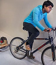 Sixteen-year-old Anurudh Ganesan from Clarksburg, Md. shows off his invention, the VAXXWAGON, a wheel-powered cooling system that keeps vaccines viable during the final stages of transport to remote locations.