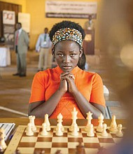 Madina Nalwanga concentrates at the chess board in her role as the chess prodigy Phiona Mutesi in the new Disney film 'Queen of Katwe.'
