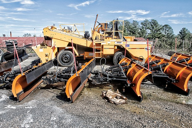 This photo shows a line of snowplows and the large Rosco gravel chip spreader that the Richmond Department of Public Works has left parked for years. Location: The department's Hopkins Road compound in South Side.