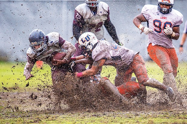 Virginia Union University junior Kevin Green carries the ball through the mud bowl during the Panthers' homecoming game last Saturday at Hovey Field. The Panthers beat the Lincoln University Lions 39-6.