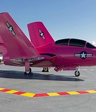 """An F9F-8 Cougar, painted in a vivid pink shade called """"Heliconia,"""" is on display on the flight deck of the USS Lexington in Corpus Christi, Texas. It's all in support of Breast Cancer Awareness Month, so the jet will be on exhibit on the deck through October 31, 2016. The pink paint job isn't permanent. Liquid dishwashing soap applied to the paint will allow it to be removed."""