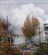 A powerful natural gas explosion rocked the Northwest 23rd Street shopping district Wednesday, injuring eight people and igniting a fire that sent a huge plume of smoke over the heart of the city. (AP photo)