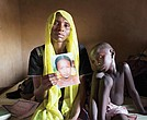 Rachel Daniel, 35, holds a photo of her 17-year-old daughter, Rose, who was abducted with more than 200 classmates on May 21, 2014, by Boko Haram militants from her school in Chibok, Nigeria. Rose's brother, Bukar, 7, sits with his mother.