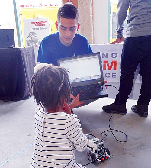 Ardit Briskaj, a junior at Boston International High School, shows 4-year-old Blake Canty how to do some robotics programming at the Build BPS open house held Oct. 28-29 at the Bruce C. Bolling Building in Dudley Square.