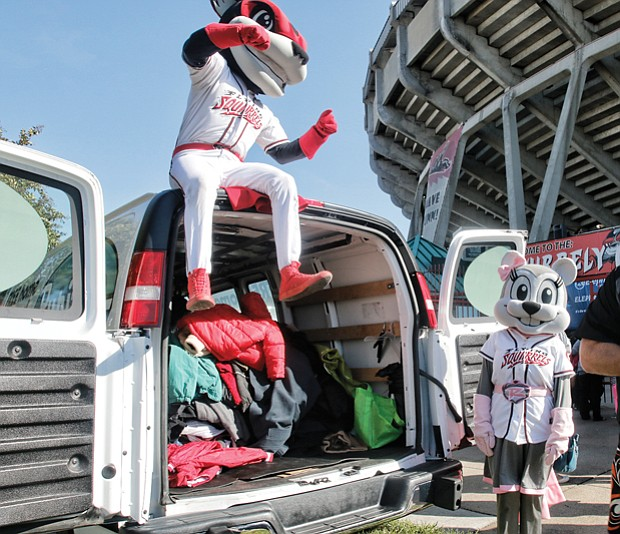 "Warming hearts one coat at a time // Todd ""Parney"" Parnell, vice president and chief operating officer of the Richmond Flying Squirrels, works with team mascots Nutzy, left, and Nutasha to load coats in a van last Saturday during the 8th Annual Coats for Kids and Ballpark Warming Party at The Diamond. 