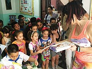 Susan Leger Ferraro distributes books to children as part of a partnership with Sergio Luis Ferriol Rios Elementary school in Old Havana, Cuba. Books were donated in partnership with First Book in Washington D.C. and Yanitzia Canetti, a Cuban author and publisher.