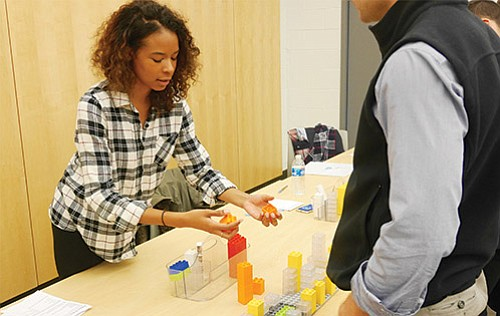 """Yaira Matos, a member of Imagine Boston 2030's community engagement team, helps attendees experiment with hands-on city planning models before an Oct. 26 data presentation, part of the city's """"Boston by the Numbers"""" series."""