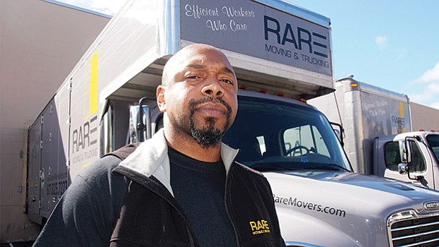 Kemaul Reid of RARE Moving & Trucking stands in front of one of the company's 7 trucks.
