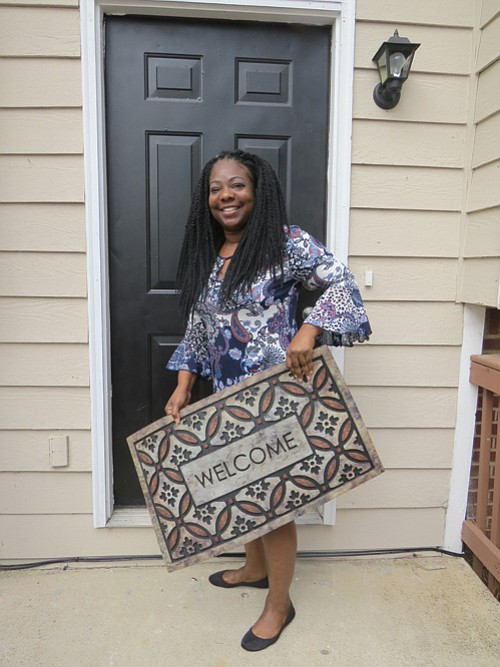 LaKesha Head holds the doormat she received from officials with the nonprofit ANDP and Bank of America, which provided down payment assistance.