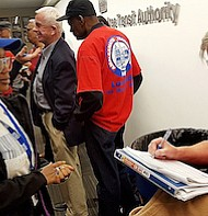 Tamia Small (left), a member of Project Retail, waits to collect a petition being signed by a member of the Amalgamated Transit Union-Local 689 at Metro headquarters in Northwest on Nov. 17.