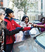 Shelia Turner (right) gives bags of food for her donation to NBC4 anchor Pat Lawson-Muse during the Food for Families drive in northwest D.C. on Nov. 21.