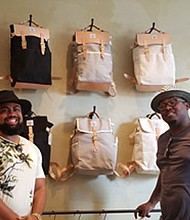 """Jason Bass (left) and Aaron Jones (right) are guilty of """"treason."""" They have defied the status quo by """"going against the grain."""" Jones and Bass are the men behind Treason Toting Company. Located at 1714 Thames Street in Fells Point, the company specializes in domestically manufacturing backpacks and other high quality travel accessories."""