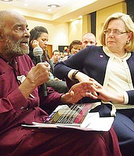 Former state Rep. Mel King speaks while Eastern Bank Executive Vice President Nancy Stager, who funded the reprinting of 'Chain of Change,' looks on during a forum at Northeastern University in November.