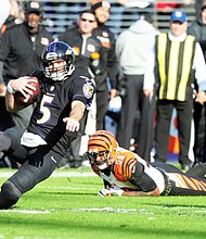 Joe Flacco slides to avoid being tackled by a Bengals defender during a game in the 2016 NFL Season.
