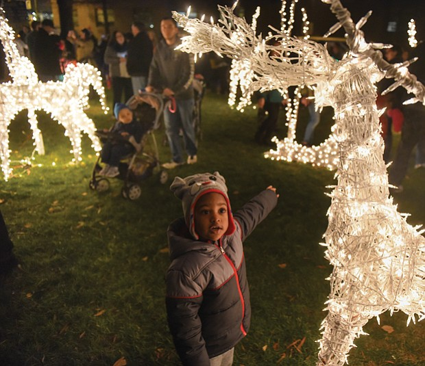 Josiah Nicholas, 2, reaches out to touch a lighted reindeer during Friday's Grand Illumination at the James Center.