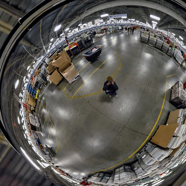 Employees work among a maze of conveyor belts and sorting machines in the huge building that is the size of 12 football fields and handles mail from Central and Eastern Virginia. Left, Free Press photographer Sandra Sellars seeks to give a sense of the building's size by photographing a portion of the center reflected in a ceiling mirror.