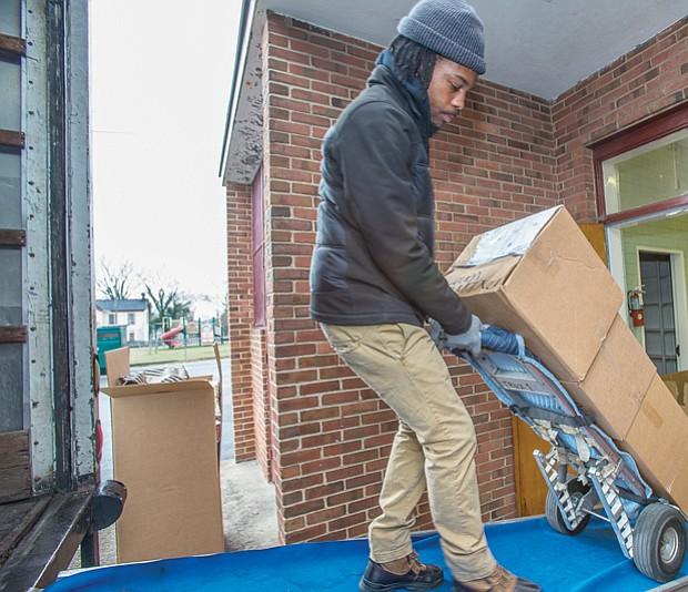 Isaac Lee, left, loads a truck with boxes Saturday from Norrell School Annex at 201 W. Graham Road in North Side. The annex and the nearby A.V. Norrell Elementary School building, which have been used as office space in recent years, are being closed to help Richmond Public Schools save money. The move is to be completed by February, and the buildings are to be returned to ownership by the City of Richmond.