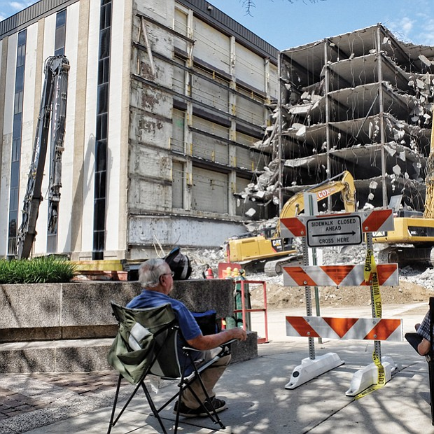 Spectators have a ringside seat as workers use powerful machines to demolish the parking deck of the vacant Richmond Plaza building at 7th and Cary streets in Downtown in August to make way for a 20-story office tower for Dominion Resources.