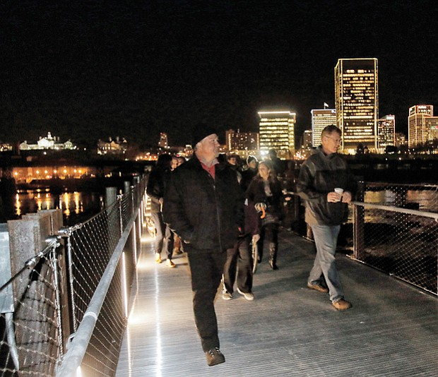 The first pedestrians stream across the newly opened T. Tyler Potterfield Memorial Bridge over the James River following the ribbon-cutting in December during the Grand Illumination in Downtown.