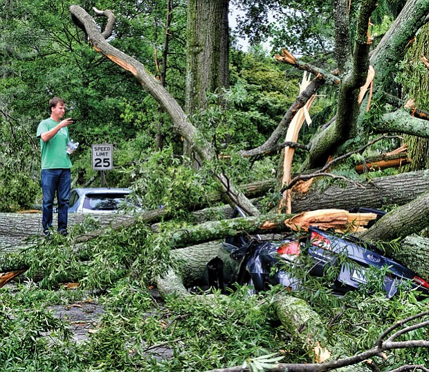 Brad Spangler takes a closer look at a car crushed under trees felled by a June storm that packed 70 mph winds, dropped 1.6 inches of rain and knocked out power to nearly 120,000 homes and businesses in Richmond and Henrico County. Location: Seminary and Claremont avenues in North Side.